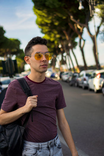 Young man wearing sunglasses standing against car