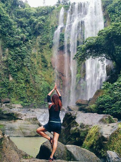 Full length of woman exercising near waterfall