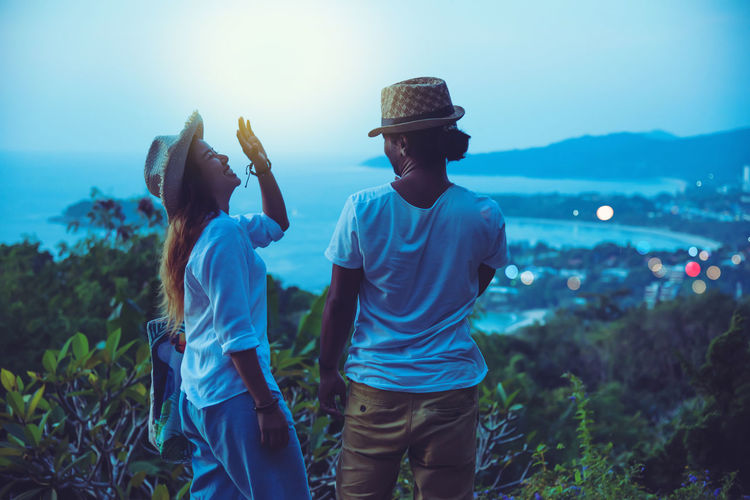 Happy couple looking at sea while standing on mountain