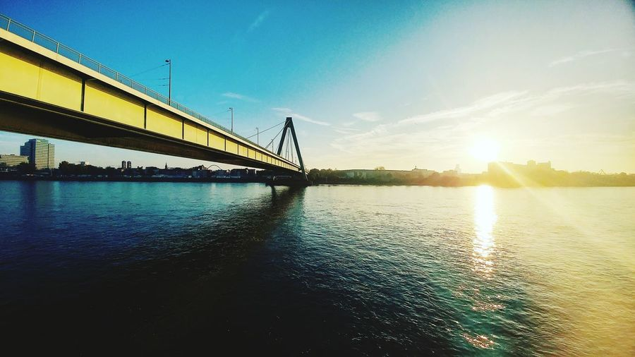 Bridge - Man Made Structure Water Sky Sunrise No People Architecture Day Architecture River City Reflection Sunny Majestic Water Surface Built Structure Sunlight Suspension Bridge Modern Illuminated Sun Idyllic Tranquility Panoramic Shot