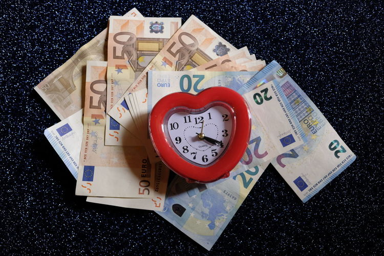 Directly above shot of alarm clock on european union currencies at table