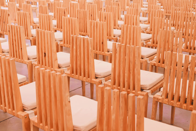 Wooden chairs in a row in a church. Wood - Material No People Brown Indoors  Arrangement Seat Chair Close-up In A Row Chair Modern Row Wooden Wood Church Empty Conference Room Ferniture Interior Vintage