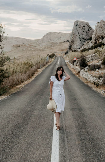 Front view of beautiful young woman in white dress standing on open road.