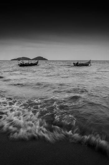 Mid distance view of fishing boats moored in sea against sky