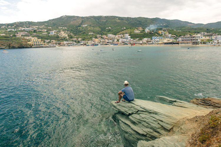 Man on rock by sea against mountains
