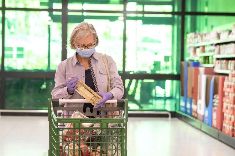 Senior woman wearing flu mask standing in store