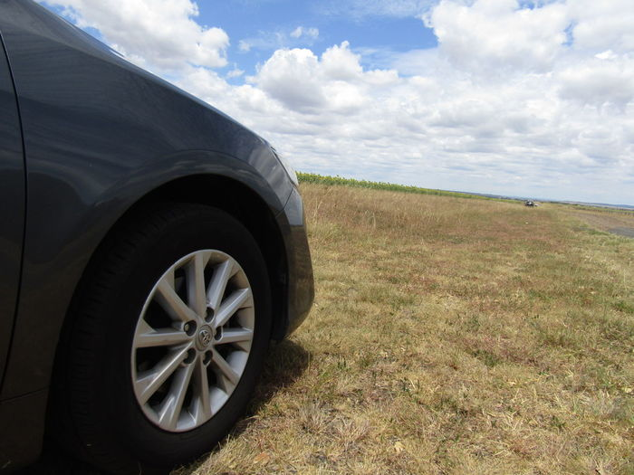 Close-up of tire on landscape against cloudy sky