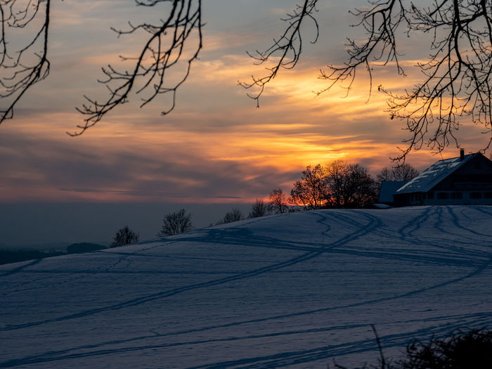 Scenic view of snow covered landscape against orange sky