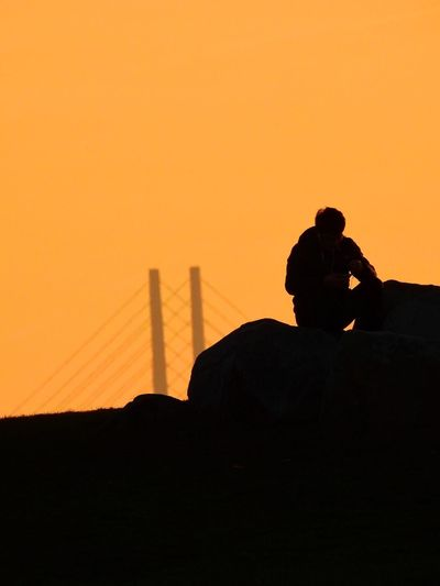 Silhouette man photographing on landscape against orange sky