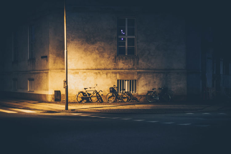 Bicycle by illuminated building at night