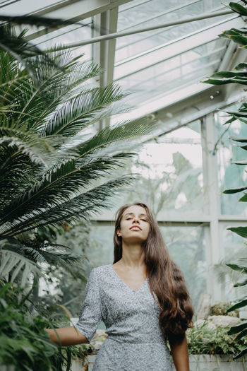 Front view of a young woman amidst plants