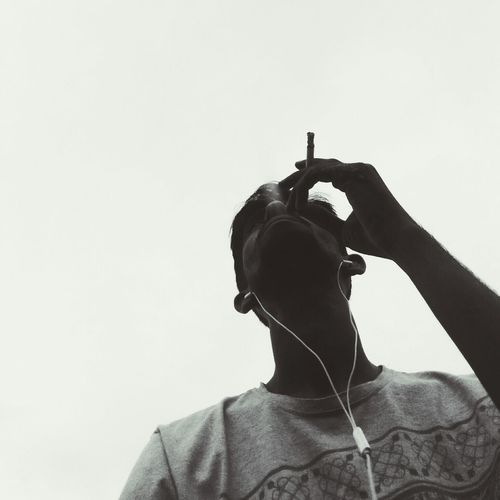 Low angle view of man smoking cigarette while listening to music against clear sky