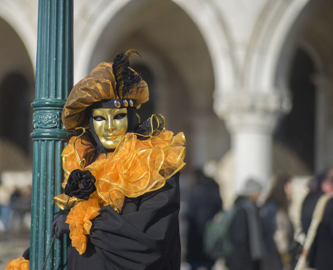 Person in costume while wearing venetian mask at venice carnival