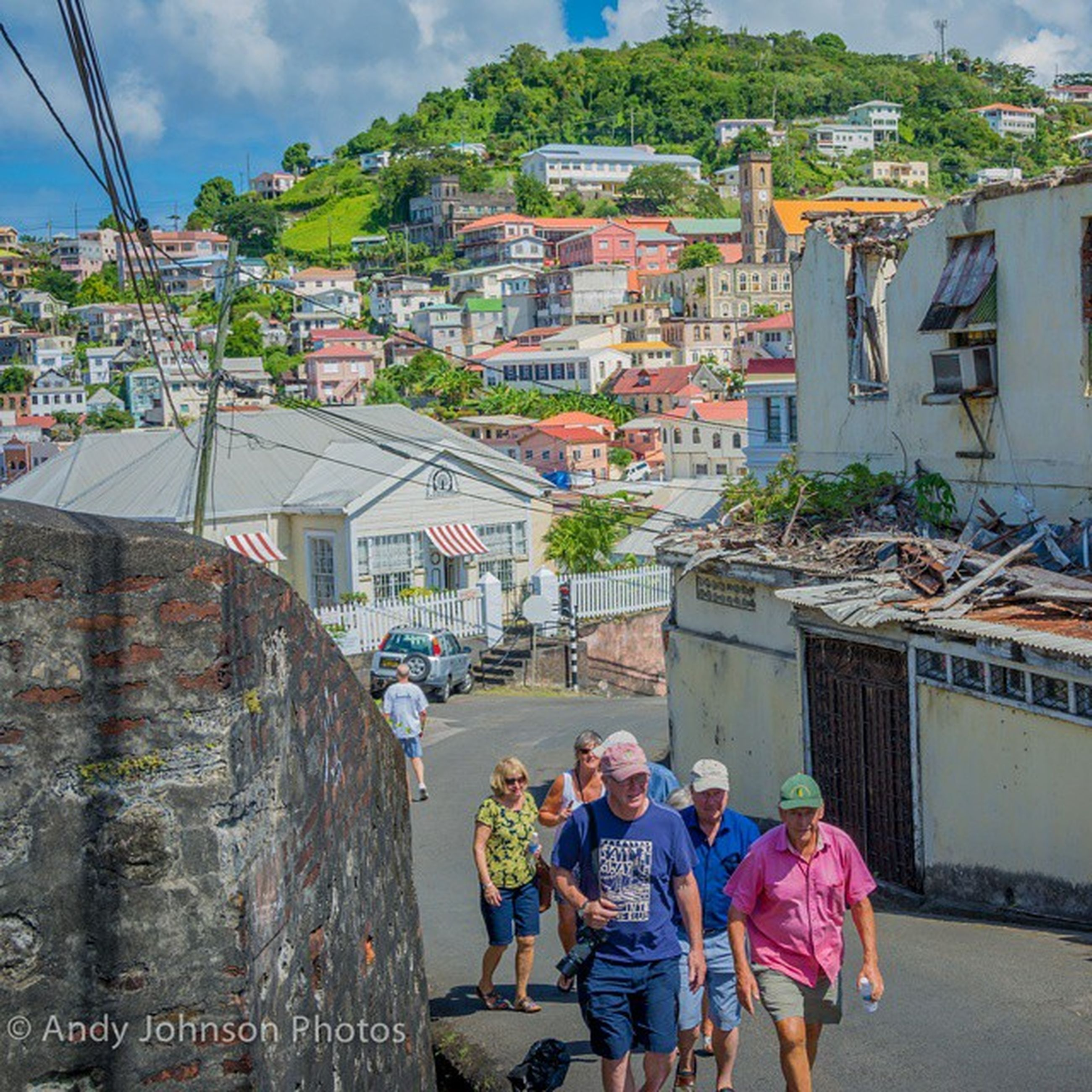 building exterior, architecture, built structure, lifestyles, men, person, leisure activity, walking, large group of people, sky, street, residential structure, residential building, rear view, city, casual clothing, town, house, city life
