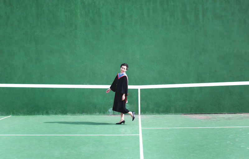 Full length portrait of young woman standing at tennis court