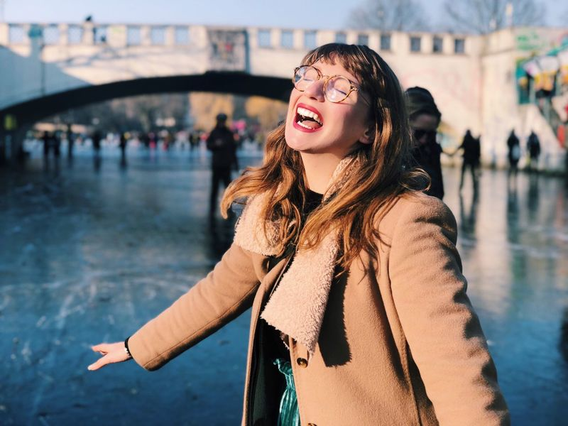 Young Woman standing on frozen canal, laughing. Canal Frozen Lake Real People Young Adult One Person Lifestyles Beautiful Woman Leisure Activity Outdoors Only Women Happiness Young Women Warm Clothing Cheerful City Life City Smiling Beautiful People Day Women