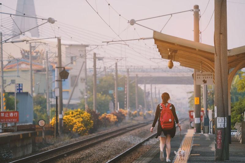 Rear view of woman walking on railroad tracks against sky