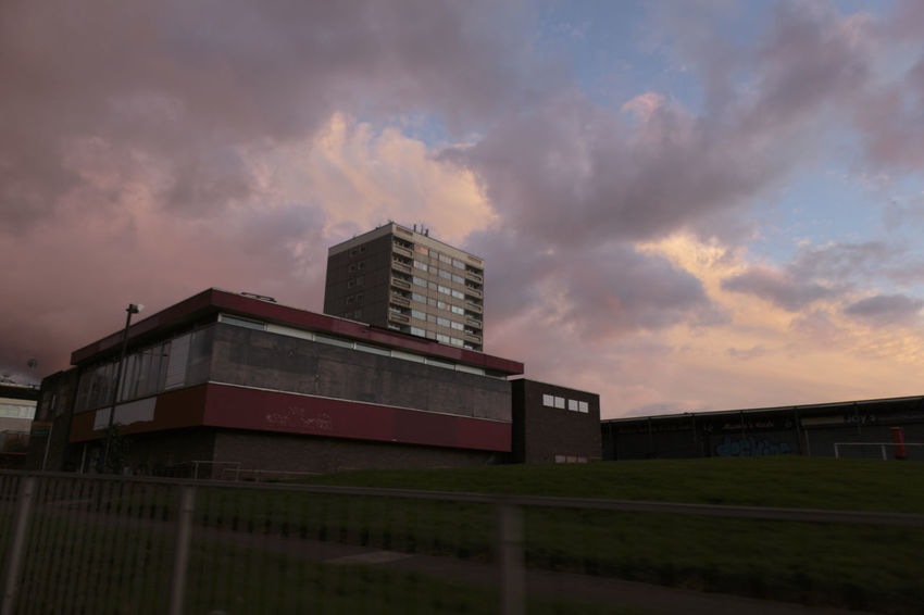 An old unused modern build pub on the outskirts of a large run down housing estate on the edge of the Birminghm, with a tower block towering over it against dark forboading clouds. Abandoned Buildings Architecture Boarded Up Brooding Building Exterior City Cityscape Cloud - Sky Clouds And Sky Dark Day Daytime Deralict Low Key Lighting Modern No People No People, Outdoors Outside Red Color Rundown Sky Storm Cloud Urban