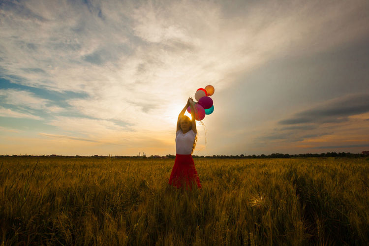 Portrait of woman holding balloons against sky