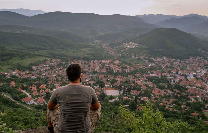 Rear view of man looking at town while sitting on mountain