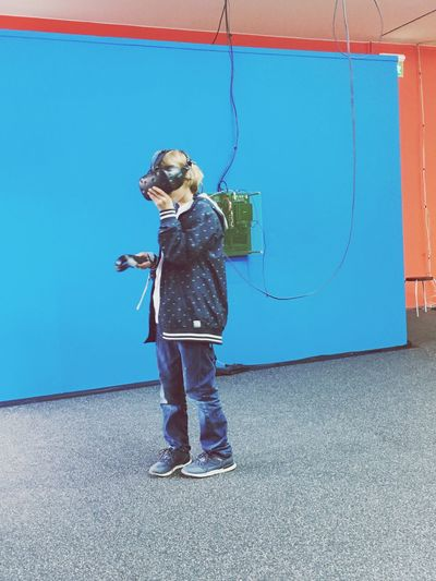 Full length of girl wearing virtual reality headset against blue wall