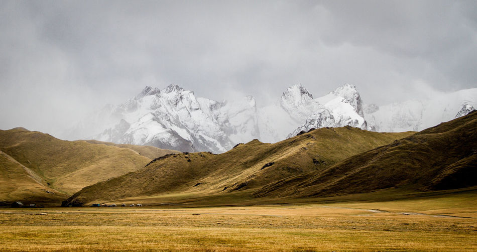 Scenic View Of Landscape Against Snowcapped Mountains