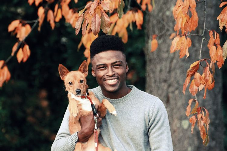 Portrait of smiling man with dog against autumn leaves