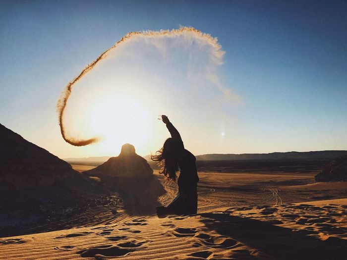 Woman throwing sand at desert against sky