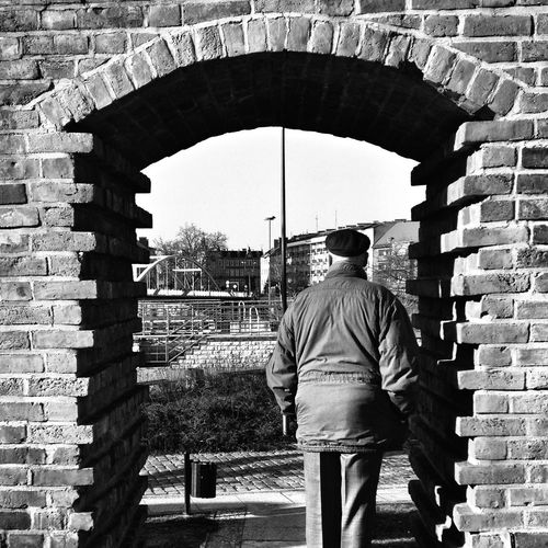 Rear View Of Man Standing Below Arch