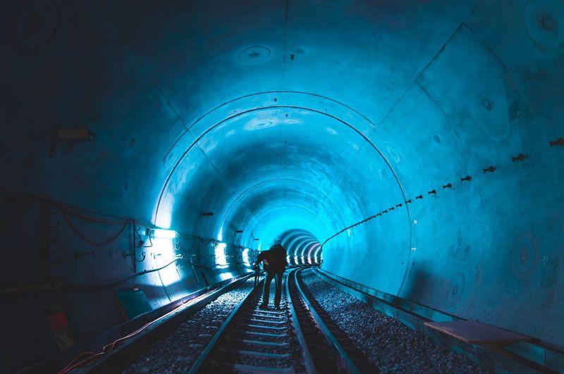Man standing in illuminated tunnel