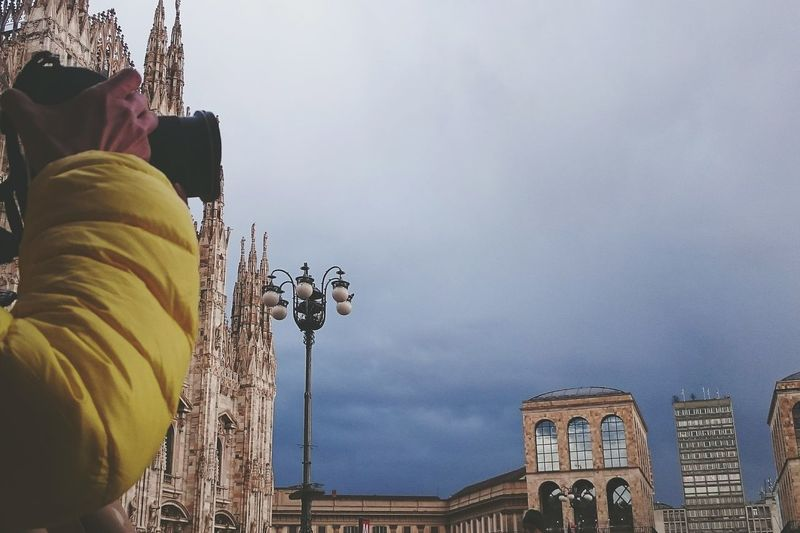 Cropped image of photographer photographing by duomo di milano against cloudy sky