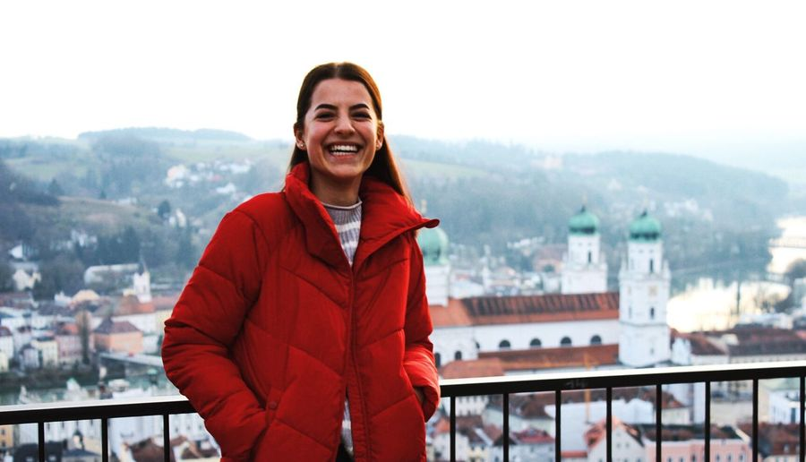 Portrait of smiling young woman in red jacket standing against cityscape