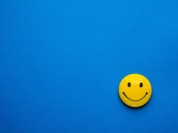 High angle view of smiling toy on blue wall