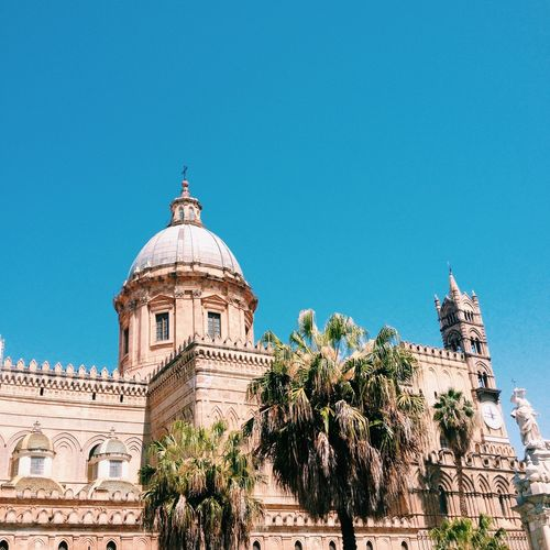 Low angle view of palermo cathedral against clear blue sky