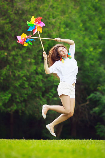 Portrait of beautiful smiling woman holding pinwheel toys while jumping on field