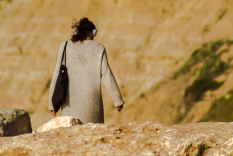 Rear view of woman perching on rock