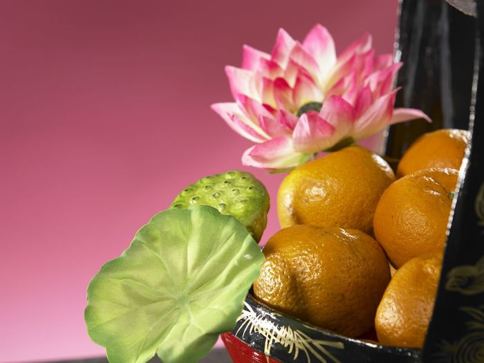 Close-Up Of Oranges In Basket Against Pink Background