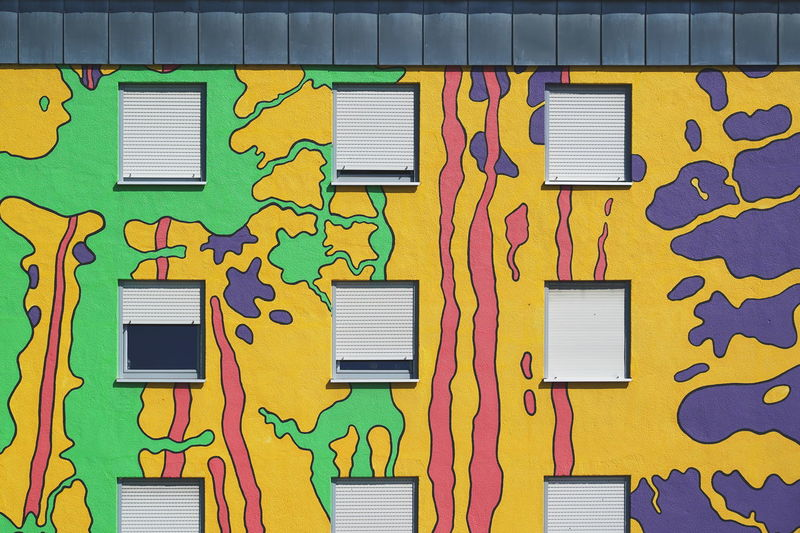 Full frame shot of multi colored wall by building