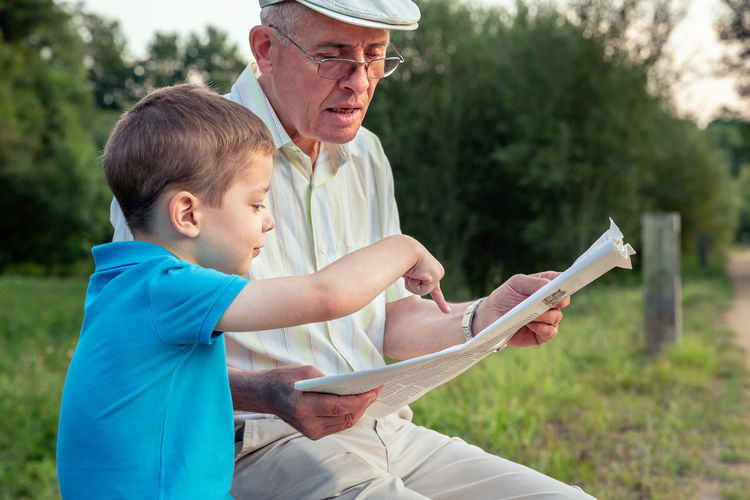 Closeup of senior man reading newspaper and cute child pointing an article with his finger over a nature background. Two different generations concept. Mature Caucasian Age Hat Parent Together Education Sitting Male Adult Background Defocused Happy Leisure Lifestyle Old People Real Two Elderly Nature Family Learning Teaching Generation Closeup Outdoors Grandparent Grandfather Grandchild Grandson Park Bench Article Notice Report Hand Finger Pointing Looking Reading Paper News Newspaper Boy Kid Child Man Senior