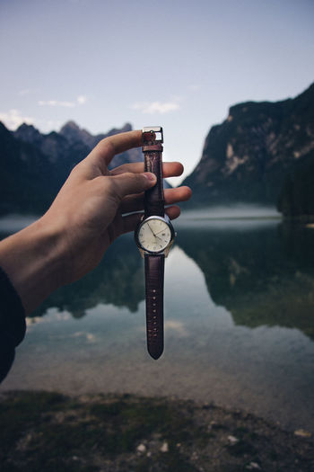 time Close-up Day Finger Focus On Foreground Hand Holding Human Body Part Human Finger Human Hand Lake Leisure Activity Lifestyles Mountain Nature One Person Outdoors Real People Sky Water