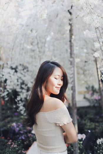 Young woman smiling while standing against white flowering trees at park