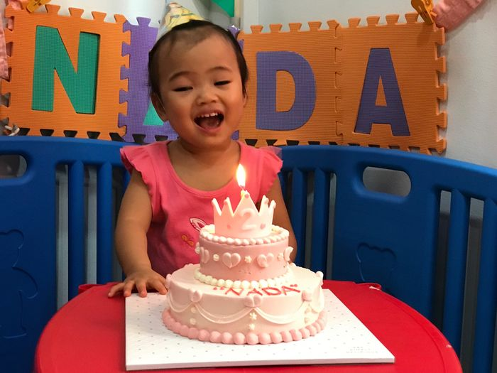 Cute baby girl looking at burning candle on birthday cake