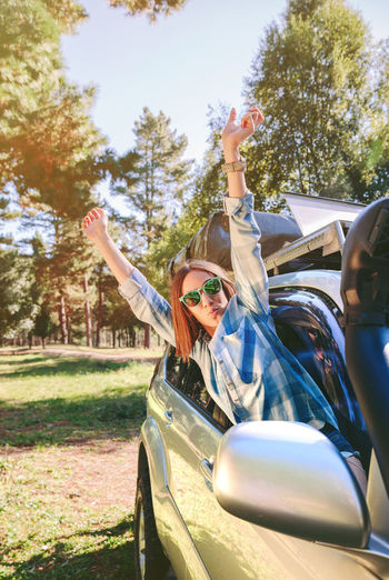 Portrait of happy young woman raising her arms through the window car in a sunny day over a nature background. Friends Fun Laughing Nature Passenger Travel Trip Woman Caucasian Cheerful Crazy Friendship Girl Inside Leisure Lifestyles One Person Raising Arms Real People Roadtrip Sunglasses Togheter Vehicle Interior Vertical Window Car