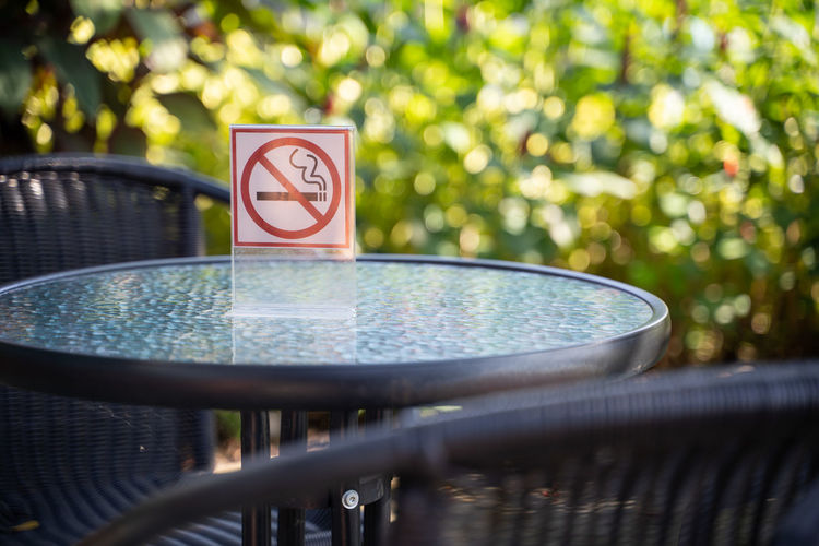 Absence Close-up Communication Day Focus On Foreground Green Color Guidance Information Information Sign Nature No People No Smoking Sign Outdoors Plant Railing Selective Focus Sign Sunlight Table Water