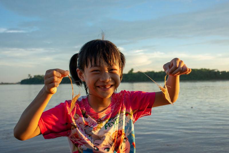 Smiling girl holding shrimps at lake