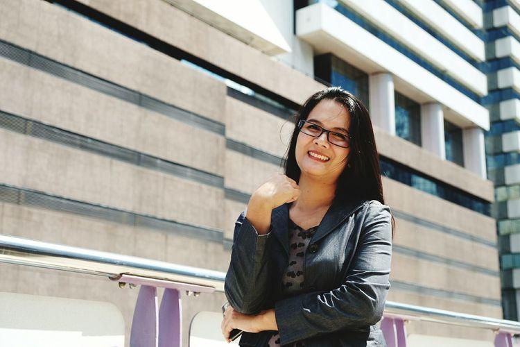 Portrait of smiling businesswoman standing against building