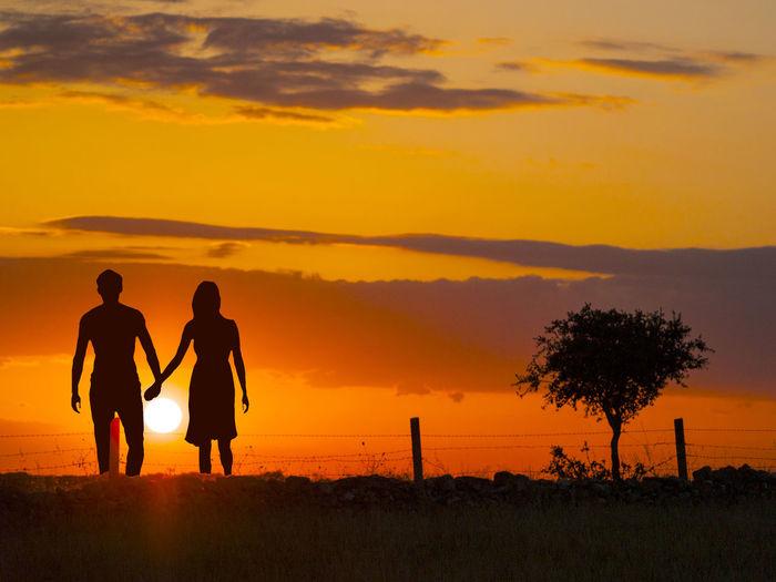 Silhouette couple walking on field against orange sky
