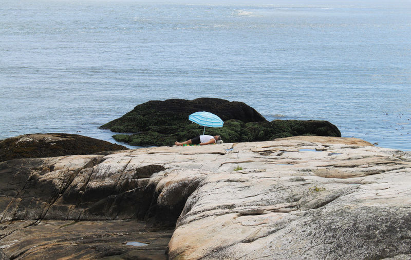 a man sleeps on a rock near to Vancouver, Canada Allein Blue Calm Coast Felsen Idyllic Küste Landscape Meer Nap Nature Parasol Rock - Object Rock Formation Schlaf Schlafen Sea Siesta Sleeping Sonnenschirm The KIOMI Collection Tranquil Scene Tranquility Vacations Water