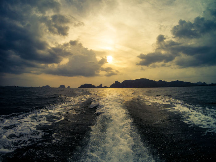 View of the sunset from a long tail boat. Railay beach on the background. Krabi, Thailand. Krabi Railay Sunset_collection Thai Thailand Beauty In Nature Boat Cloud - Sky Idyllic Nature No People Outdoors Scenics - Nature Sea Sky Sun Sunlight Sunset Trail Tranquil Scene Tranquility Water