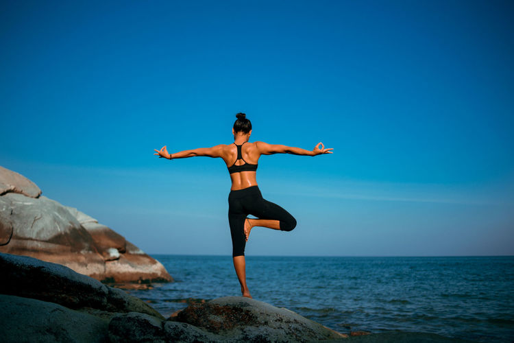 Full Length Of Woman Doing Yoga On Rock Against Sea